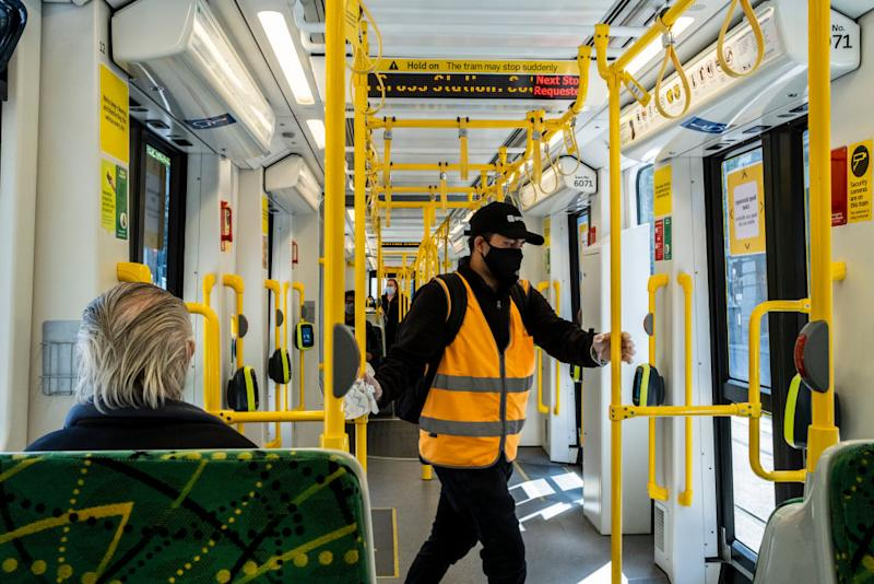 A worker wearing a face mask sanitises the tram during the lockdown in Melbourne. Source: Getty