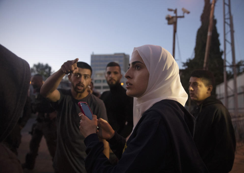 Palestinian activist Muna al-Kurd, center, stands with other activists as Israeli police approach their friends repairing a mural that was defaced by a Jewish settler, in the Sheikh Jarrah neighborhood of east Jerusalem, where Palestinian families face imminent eviction from their homes by Israeli settlers, Monday, May 24, 2021. On Sunday, June 6, 2021, Israel arrested and later released al-Kurd in the contested Sheikh Jarrah neighborhood of Jerusalem, a day after forcefully detaining a prominent journalist there. (AP Photo/Maya Alleruzzo)