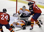 Philadelphia Flyers defenseman Luke Schenn (22) blocks a shot by Florida Panthers left wing Tomas Fleischmann (14) in the second period of an NHL hockey game in Sunrise, Fla., Saturday, Nov. 1, 2014. (AP Photo/Alan Diaz)