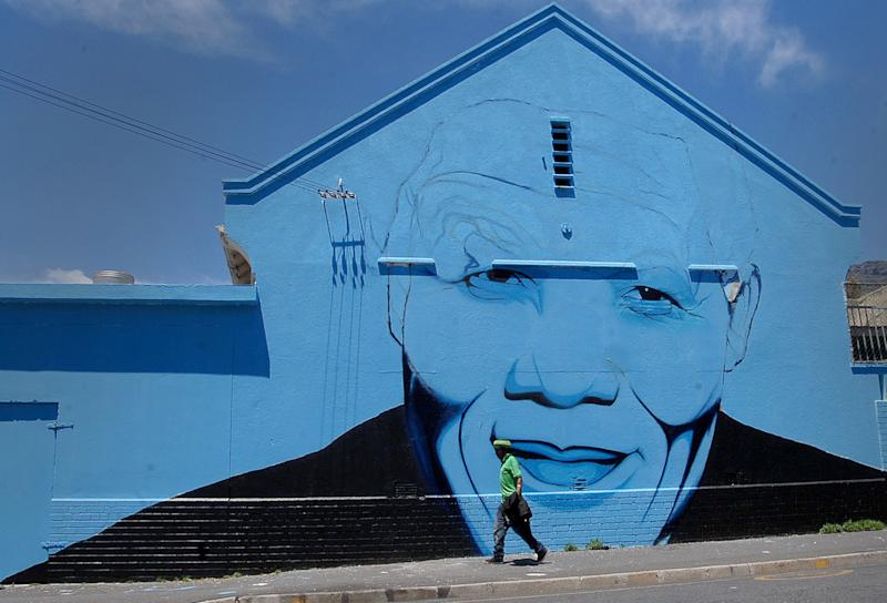 A pedestrian passes a wall mural of former president Nelson Mandela in Cape Town South Africa, Tuesday, Nov. 18, 2013. The South African president's office says that Jacob Zuma visited the 95-year-old anti-apartheid leader Nelson Mandela on Monday morning and said that he remains in stable but critical condition. Zuma's office says Mandela continues to respond to treatment at his home in Johannesburg. (AP Photo/Masixole Feni)