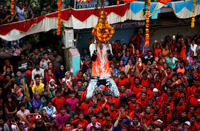 <p>A devotee hangs from a clay pot containing curd after breaking it during the Hindu festival of Janmashtami, marking the birth anniversary of Hindu Lord Krishna, in Ahmedabad, India, September 4, 2018. REUTERS/Amit Dave </p>