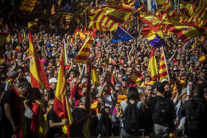 Nationalist activists march with Catalan, Spanish and European Union flags during a mass rally against Catalonia's declaration of independence, in Barcelona, Spain, Sunday, Oct. 29, 2017. Thousands of opponents of independence for Catalonia held the rally on one of the city's main avenues after one of the country's most tumultuous days in decades. (AP Photo/Santi Palacios)