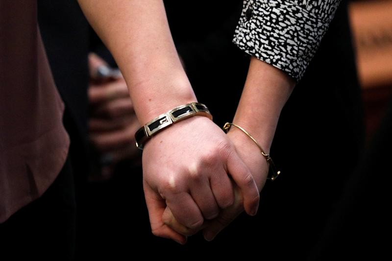 Victims and former gymnasts Maddie and Kara Johnson hold hands as they speak at the sentencing hearing. (Brendan McDermid/Reuters)