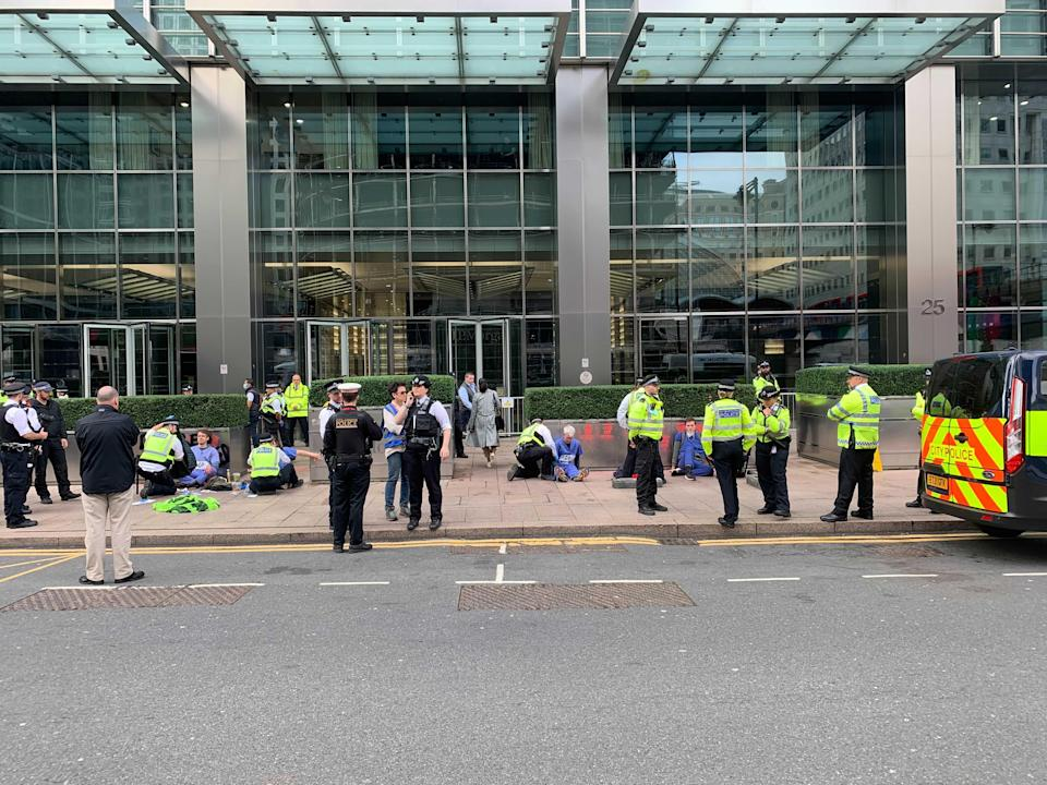 Protesters with their hands stuck to the pavement outside JP Morgan (The Independent)
