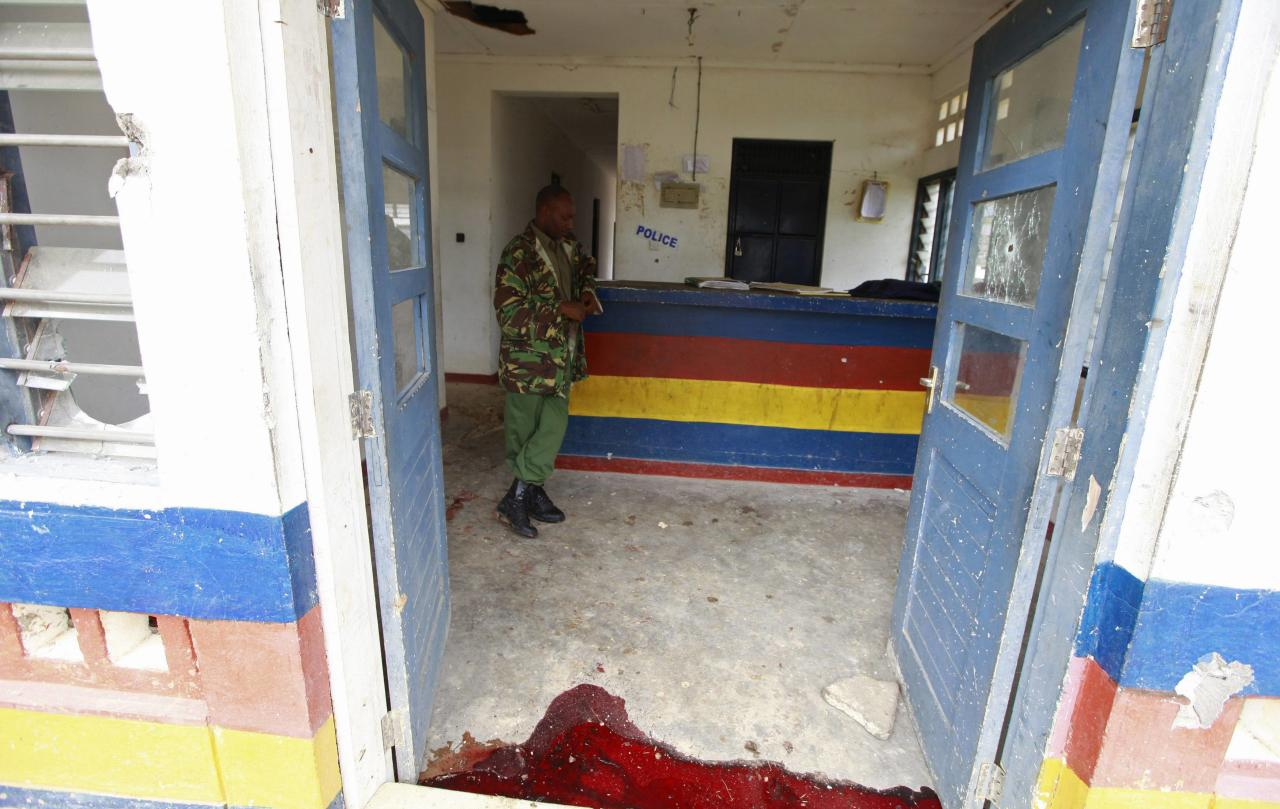 A policeman stands near a pool of blood where his colleague was killed during an attack by gunmen who raided Gamba police station at the Kenyan coast, July 6, 2014. Gunmen killed at least 29 people in raids on two separate areas on the Kenyan coast, the interior ministry said on Sunday. The Somali Islamist militant group al Shabaab said it had staged an attack on Saturday evening in the coastal area, and it had broken into the police station at Gamba and freed suspects from the detention cells. REUTERS/Joseph Okanga (KENYA - Tags: CIVIL UNREST CRIME LAW)