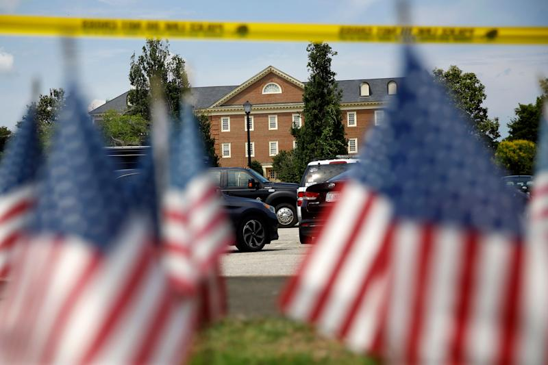 American flags that are part of a makeshift memorial stand at the edge of a police cordon in front of a municipal building that was the scene of a shooting, Saturday, June 1, 2019, in Virginia Beach, Va. DeWayne Craddock, a longtime city employee, opened fire at the building Friday before police shot and killed him, authorities said. (AP Photo/Patrick Semansky)