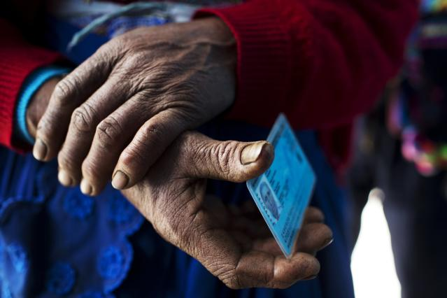 <p>A Quechua indigenous woman holds her identification card before voting during general elections in Iquicha, Peru, April 10, 2016. (Photo: Rodrigo Abd/AP) </p>