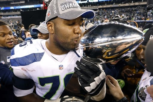 Seattle Seahawks' Russell Okung kisses the Lombardi Trophy after the NFL Super Bowl XLVIII football game Sunday, Feb. 2, 2014, in East Rutherford, N.J. The Seahawks won 43-8. (AP Photo/Paul Sancya)