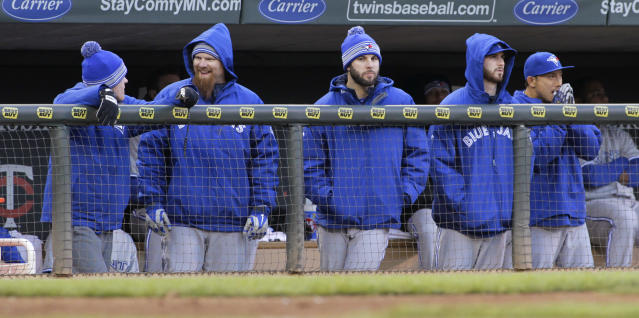 Toronto Blue Jays players are bundled up during the fourth inning of a baseball game against the Minnesota Twins, Thursday, April 17, 2014, in Minneapolis. The temperature at game time was in the upper 30s. AP Photo/Paul Battaglia)
