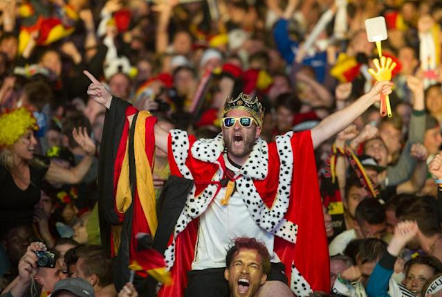 German soccer fans react after the deciding goal for Germany in the final of the Brazil World Cup 2014 between Germany and Argentina played in Rio de Janeiro, Brazil, at a public viewing area called 'Fan Mile' in Berlin, Sunday, July 13, 2014. Germany won by 1-0. (AP Photo/Steffi Loos)
