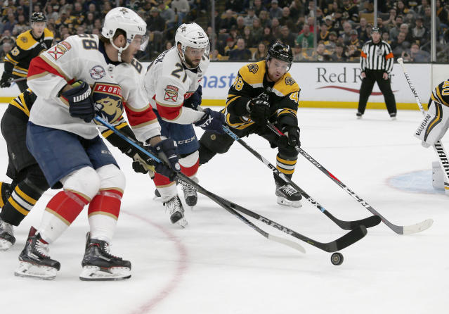 Florida Panthers left wing Mike Hoffman (68), teammate center Vincent Trocheck (21) and Boston Bruins defenseman Matt Grzelcyk (48) make a play for the puck during the first period of an NHL hockey game, Saturday, March 30, 2019, in Boston. (AP Photo/Mary Schwalm)