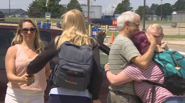 Paige MacLean, right, hugs her family after arriving at the airport on a flight from Toronto on Sunday. (Rick Gibbs/CBC - image credit)
