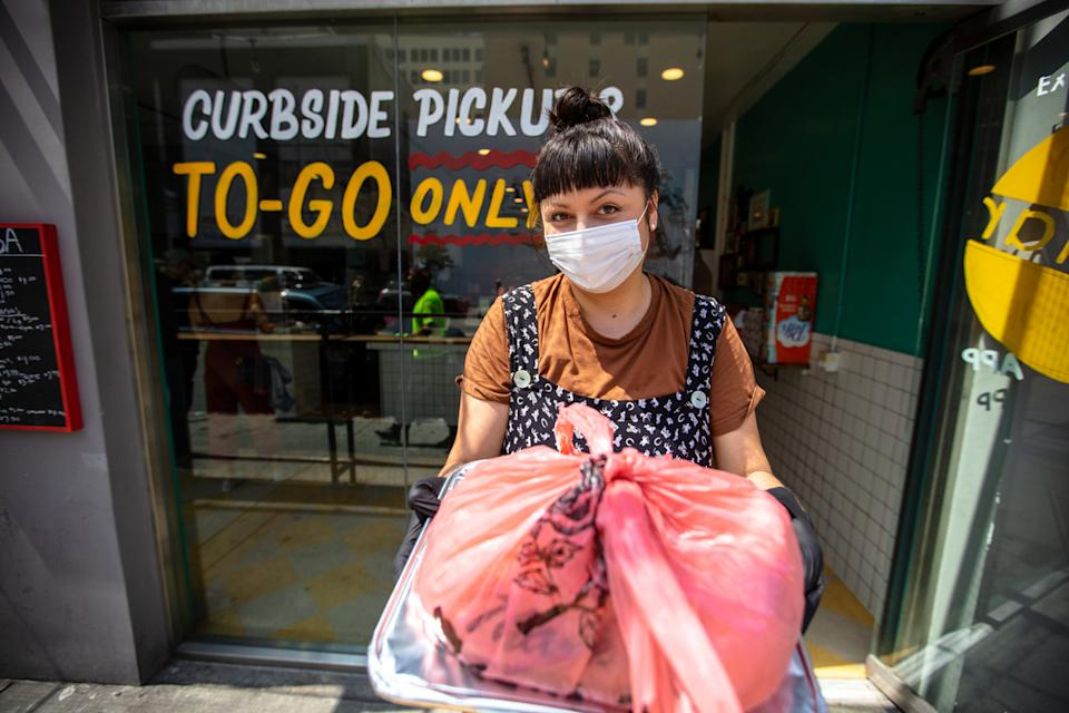 a young hispanic woman hands over a curbside order