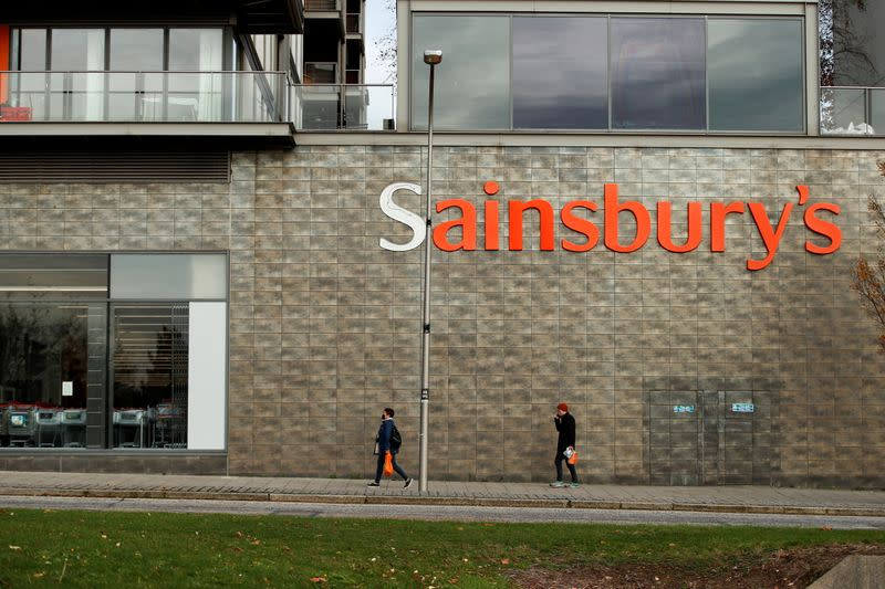 FILE PHOTO: People walk past a Sainsbury's store in Milton Keynes