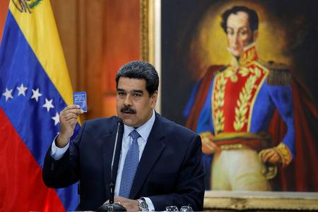 Venezuela's President Nicolas Maduro holds a copy of the National Constitution while he speaks during a news conference at Miraflores Palace in Caracas