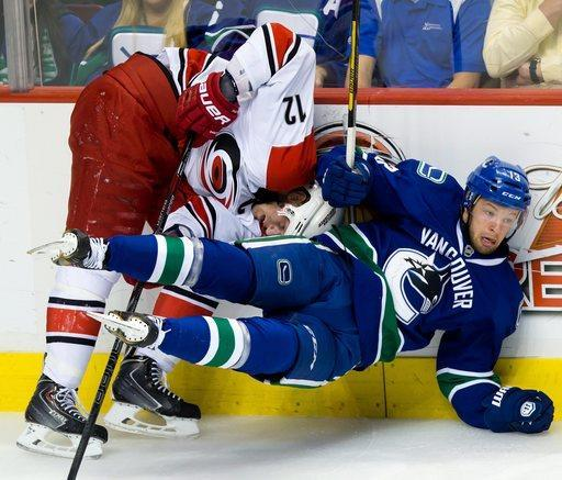 Carolina Hurricanes' Eric Staal, left, and Vancouver Canucks' Jeremy Welsh collide during the second period of an NHL hockey game in Vancouver, British Columbia on Monday, Dec. 9, 2013. (AP Photo/The Canadian Press, Darryl Dyck)
