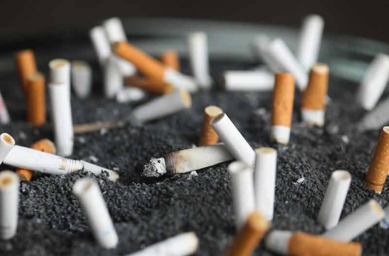 """FILE - This March 28, 2019, file photo shows cigarette butts in an ashtray in New York. Two of the hottest trends in investing are working in tandem to steer billions of dollars toward companies seen as the best corporate citizens. The sustainable investing field in its early days attracted investors by avoiding so-called """"sin stocks""""-- gun makers, cigarette manufacturers, etc. (AP Photo/Jenny Kane, File)"""