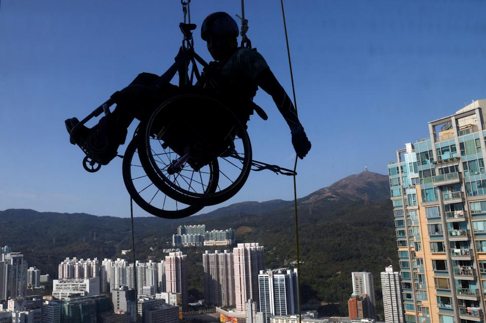 Lai Chi-wai, a paraplegic climber, attempts to climb the 320-metre tall Nina Tower using only his upper body strength, in Hong Kong, China January 16, 2021. On this attempt, Lai completed 250-meters (75/f), as he faced strong winds. Picture taken January 16, 2021. REUTERS/Tyrone Siu