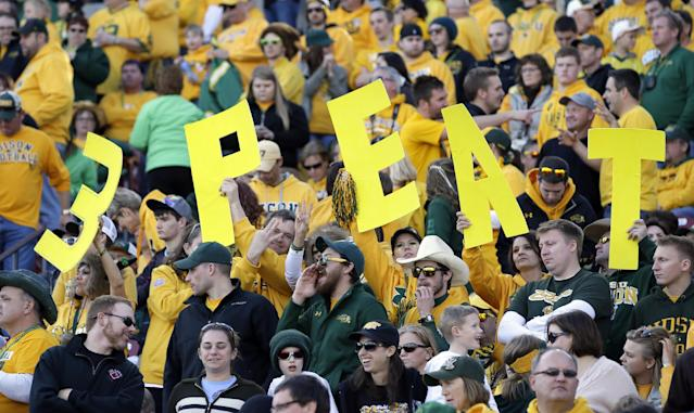 "North Dakota State fans hold up signs that read ""3 Peat"" late in the second half of the FCS championship NCAA college football game against Towson, Saturday, Jan. 4, 2014, in Frisco, Texas. NDSU won the game 35-7, making it three in a row for the university. (AP Photo/Tony Gutierrez)"