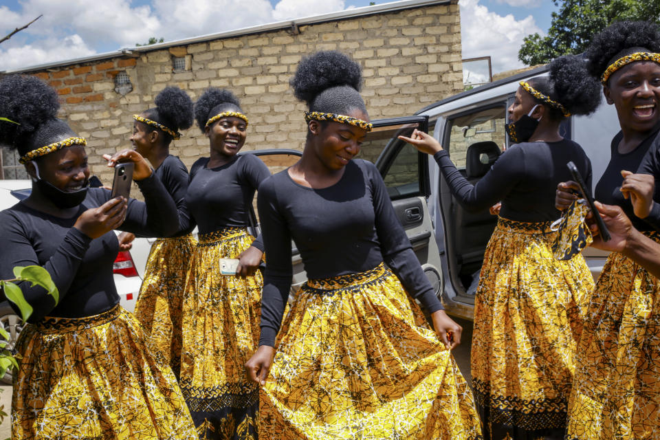 Bridesmaids share a joke as they dance at a traditional marriage ceremony in the capital Harare, Zimbabwe Saturday, March 6, 2021. Many people across Africa are rethinking big, bountiful weddings amid the economic ravages of COVID-19 and the coronavirus pandemic is forcing change in communities where family can mean a whole clan and weddings are seen as key in cementing relations between communities. (AP Photo/Tsvangirayi Mukwazhi)