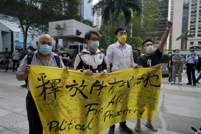 """Various defendants including pro-democracy activists Figo Chan Ho-wun, second from left, and Avery Ng, second from right, hold a banner outside a court in Hong Kong, Monday, May 17, 2021. Trial starts for Jimmy Lai and nine others, accused of """"incitement to knowingly take part in an unauthorized assembly"""" for a protest march on Oct. 1, 2019. The court has estimated 10 days for this trial. (AP Photo/Kin Cheung)"""