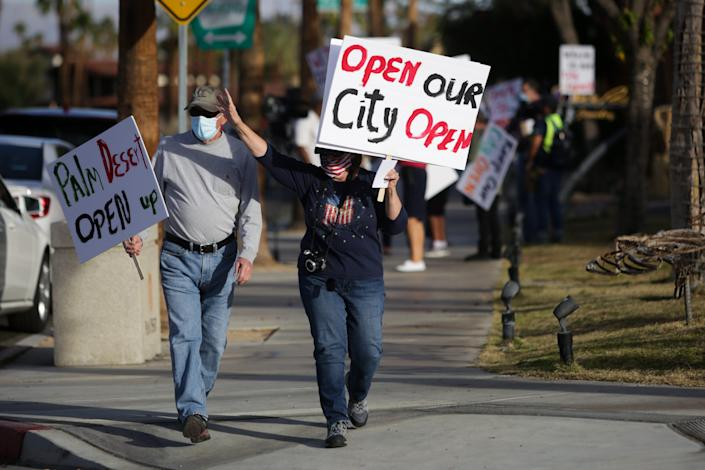 People gather on El Paseo to protest coronavirus-related business shutdowns in Palm Desert, Calif. on Wednesday, January 6, 2020.