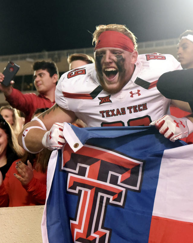 Texas Tech defensive lineman Houston Miller celebrates in the stands with fans following an NCAA college football game in Stillwater, Okla., Saturday, Sept. 22, 2018. Texas Tech won 41-17. (AP Photo/Brody Schmidt)