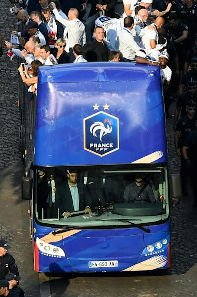 Alexandre Benalla is seen in the driver's cabin (front left) of the bus carrying France's World Cup football team during a victory parade in Paris on Monday