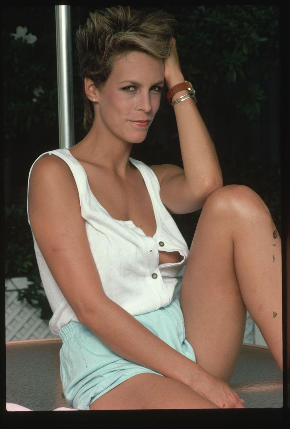 <p>Jamie Lee Curtis poses in a pair of turquoise athletic shirts and a white tank top. The actress, who rose to fame in the horror film Halloween, had just starred in A Fish Called Wanda. </p>