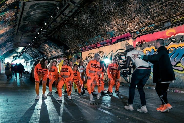 Dancers in matching orange tracksuits perform for a music video in a graffiti-covered tunnel in London