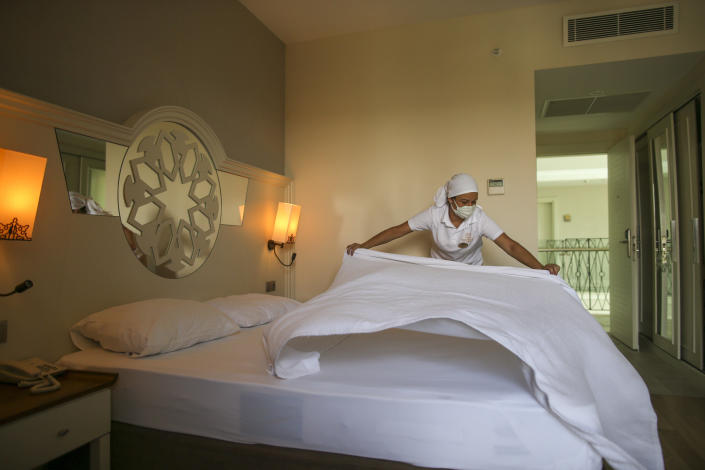 A hotel employee wearing a protective face mask prepares a room, in Antalya, southern Turkey, Saturday, June 19, 2021. Hotels in Turkey's Antalya region, a destination beloved by holidaymakers, are preparing to finally resume operations as they expect the return of international tourists after months of setbacks caused by the pandemic that halted travel. (AP Photo/Emrah Gurel)