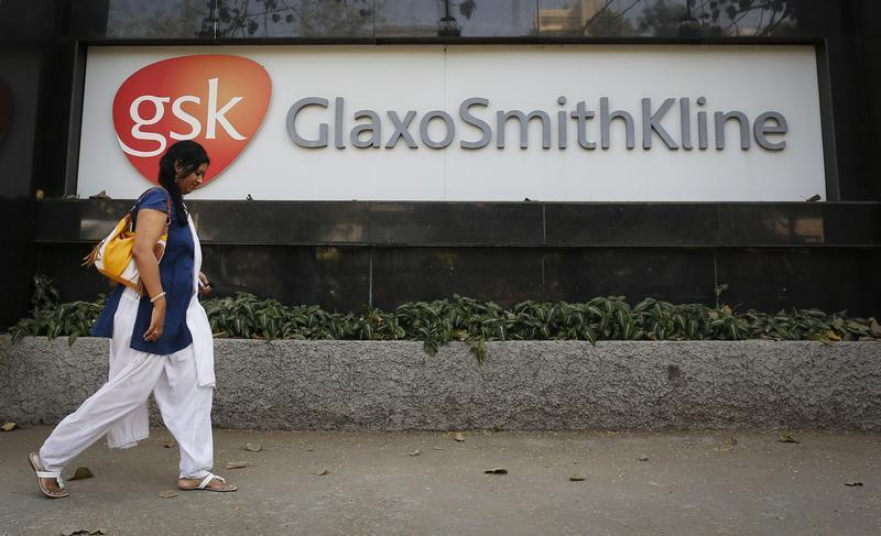 A woman walks past a GlaxoSmithKline Pharmaceuticals Ltd logo outside their headquarters in Mumbai December 16, 2013. REUTERS/Danish Siddiqui