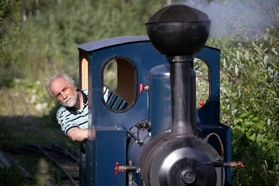 Pavel Chilin drives his steam locomotive along his own miniature personal railway in Ulyanovka village outside St. Petersburg, Russia Sunday, July 19, 2020. It took Chilin more than 10 years to build a 350-meter-long mini-railway twisting through the grounds of his cottage home about 50 kilometers (some 30 miles) outside St. Petersburg, complete with various branches, dead ends, circuit loops, and even three bridges.(AP Photo/Dmitri Lovetsky)