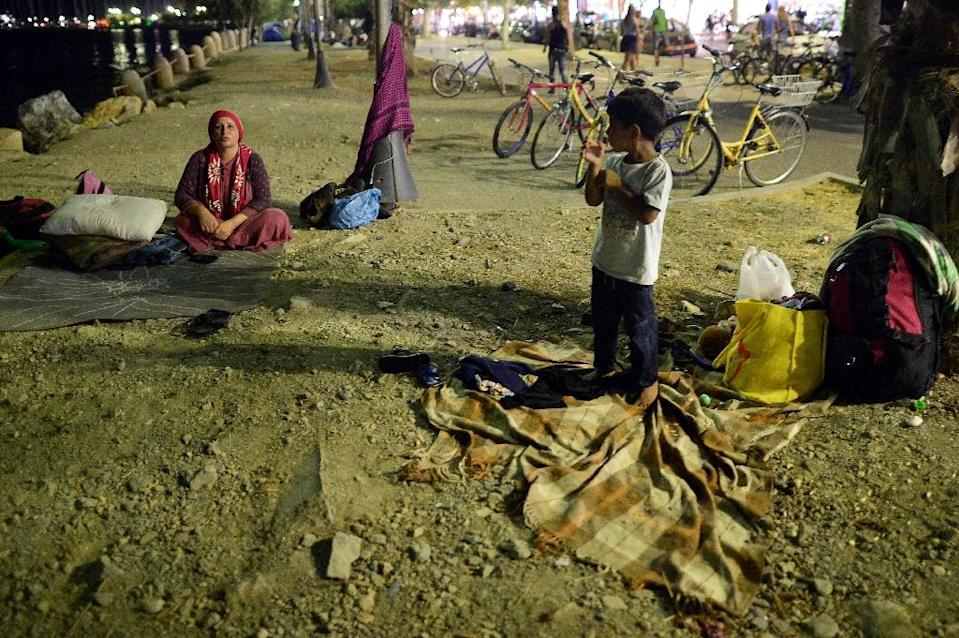 An Afghan migrant family prepares to go to sleep at their unprovisioned camp in the center of the city of Kos island, late on August 17, 2015 (AFP Photo/Louisa Gouliamaki )