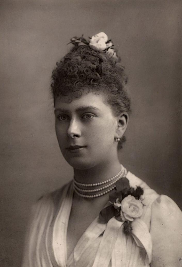 """<p>While their engagement was announced in the garden of Sheen Lodge in 1893, the details of Queen Mary's engagement ring remains unknown. Historians have been unable to find a record of or track down a ring belonging to the Queen, who reigned from 1910 until 1936, and it's <a href=""""https://www.thehistorypress.co.uk/articles/royal-engagement-rings-through-the-centuries/"""" rel=""""nofollow noopener"""" target=""""_blank"""" data-ylk=""""slk:referred to as the lost ring"""" class=""""link rapid-noclick-resp"""">referred to as the lost ring</a>. The Queen did, however, leave behind the Queen Mary Bandeau Tiara, which she wore on her wedding day and was lent to the Duchess of Sussex on her wedding day in 2018. </p>"""