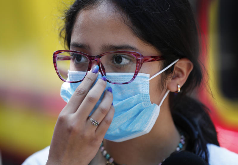 A teen wears a medical mask as a precaution against the spread of the new coronavirus, during an outing in Mexico City, Saturday, Feb. 29, 2020. Mexico's Health Department said late Friday that a new case had been confirmed in Mexico City, adding to the first two confirmed cases announced earlier that day.  (AP Photo/Marco Ugarte)