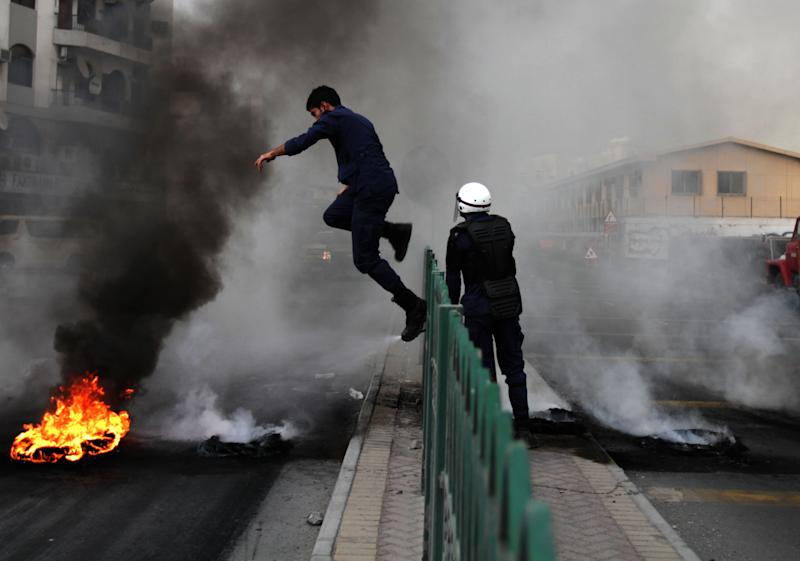 A riot policeman jumps a fence to extinguish a tire fire set by Bahraini anti-government protesters in Sehla, Bahrain, on Thursday, April 18, 2013. Organizers of Bahrain's Formula One Grand Prix, to be held Sunday, said Thursday that sporadic protests against the race and violent unrest across the Gulf nation do not pose a threat to the premier international event in the kingdom. (AP Photo/Hasan Jamali)
