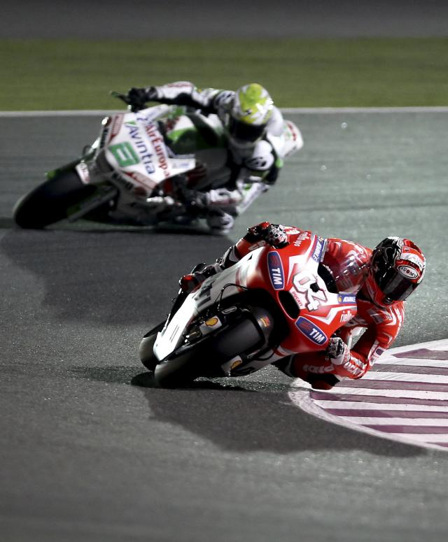 Ducati Team MotoGP rider Andrea Dovizioso (R) of Italy rides his bike next to Avintia Racing's Hector Barbera of Spain during a free practice session at the MotoGP World Championship at the Losail International circuit in Doha March 21, 2014. REUTERS/Fadi Al-Assaad (QATAR - Tags: SPORT MOTORSPORT)