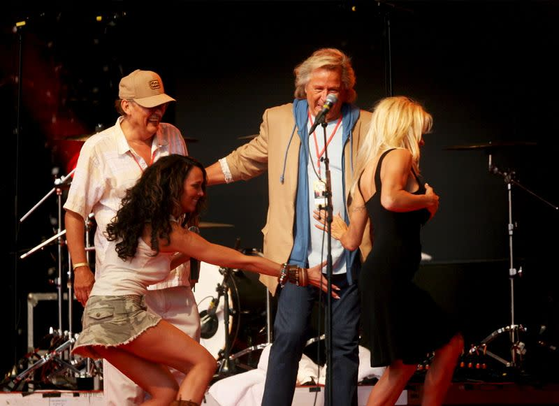 Actress Pamela Anderson plays with host Ellen Jokikunnas on stage at the Raumanmeri Midsummer Festival while her father Barry and Finnish-born fashion designer Peter Nygard look at them in Rauma