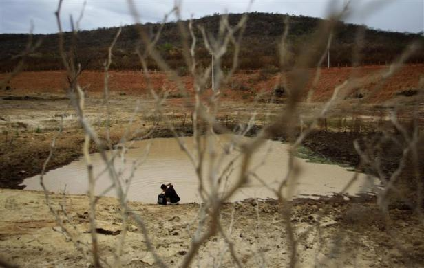 Geovani Santos collects water from a weir which has nearly dried up as a consequence of the drought in Maracas at Bahia state, northeast Brazil May 4, 2012.