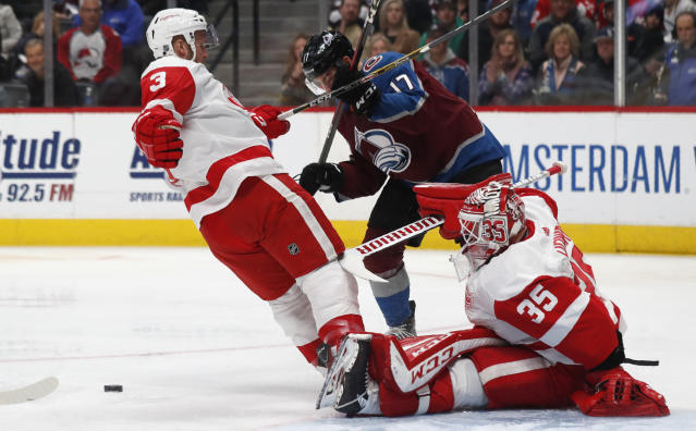 Detroit Red Wings goaltender Jimmy Howard, right, kicks out the puck after stopping a shot off the stick of Colorado Avalanche center Tyson Jost, center, as Red Wings defenseman Alex Biega covers in the first period of an NHL hockey game Monday, Jan. 20, 2020, in Denver. (AP Photo/David Zalubowski)
