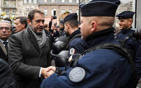 French Interior Minister Christophe Castaner (L) greets officers during the reopening of the christmas market of Strasbourg, eastern France, on December 14, 2018 - Credit: SEBASTIEN BOZON/AFP