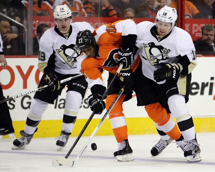 Philadelphia Flyers' Wayne Simmonds, center, gets taken off the puck by Pittsburgh Penguins' Beau Bennett, left, and James Neal, right in the second period of an NHL hockey game, Thursday, March 7, 2013, in Philadelphia. (AP Photo/Tom Mihalek)