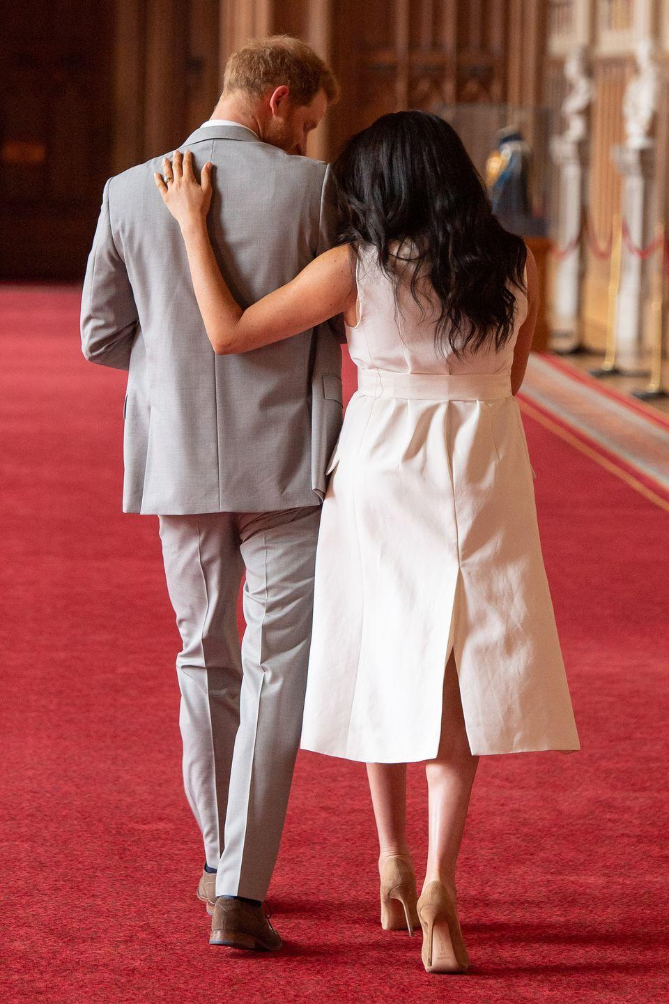 <p>Meghan put her arms around Harry (and Archie!) as they left the photocall, a family of three. </p>