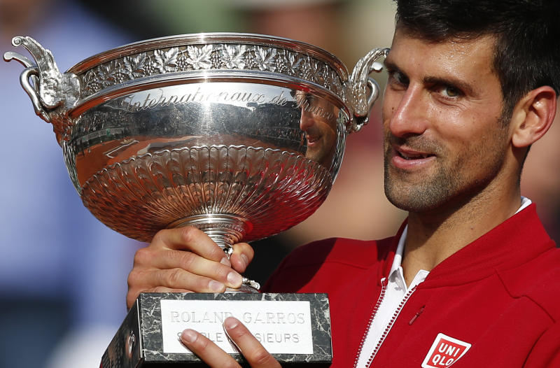 FILE - In this June 5, 2016, file photo, Serbia's Novak Djokovic holds the trophy after defeating Britain's Andy Murray in four sets 3-6, 6-1, 6-2, 6-4, in the finals of the French Open tennis tournament the Roland Garros stadium in Paris, France. (AP Photo/Christophe Ena, File)