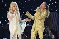 """<p>The eight-time Grammy Award winner is<a href=""""https://www.oprahmag.com/entertainment/tv-movies/a26255759/miley-cyrus-shawn-mendes-dolly-parton-tribute-grammys/"""" rel=""""nofollow noopener"""" target=""""_blank"""" data-ylk=""""slk:paid special tribute at the 2019 Grammys"""" class=""""link rapid-noclick-resp""""> paid special tribute at the 2019 Grammys</a>. Taking the stage for the first time in 18 years, Parton <a href=""""https://www.oprahmag.com/life/g25322573/celebrities-that-are-related/"""" rel=""""nofollow noopener"""" target=""""_blank"""" data-ylk=""""slk:performs alongside her goddaughter"""" class=""""link rapid-noclick-resp"""">performs alongside her goddaughter</a>, Miley Cyrus, whose dad is country legend Billy Ray Cyrus.</p>"""