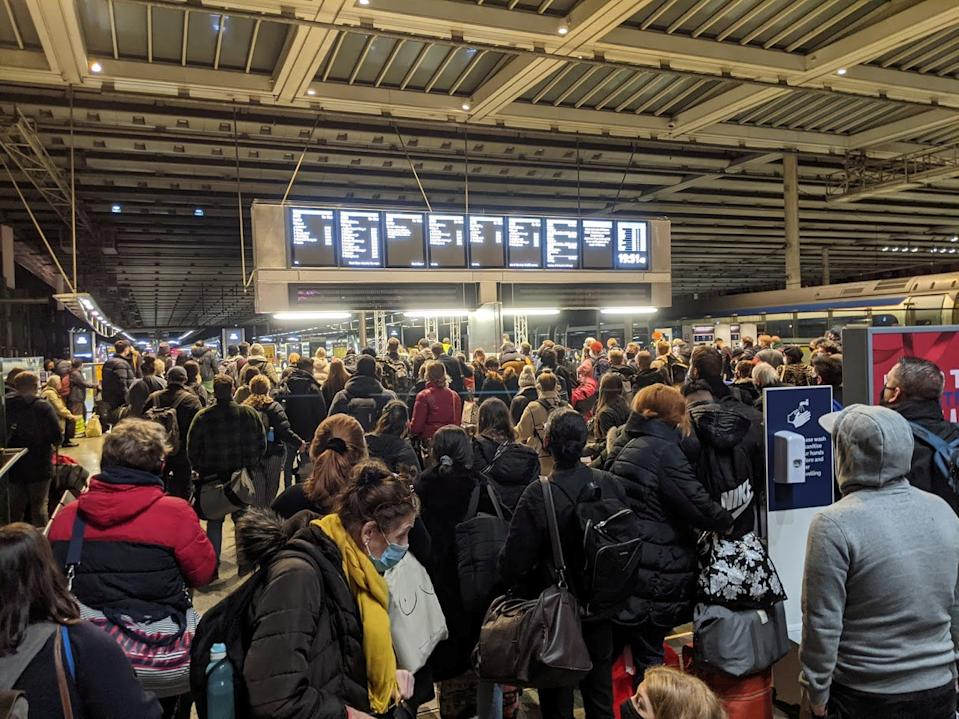 These shocking images show St Pancras train station packed with masked passengers desperate to get home for Christmas before Tier 4 restrictions hit London. See SWNS story SWOCtrain. Masked passengers can be seen clutching suitcases as they stand shoulder to shoulder with other ticket holders, rendering social distancing impossible. The shocking sight was filmed around three hours after Prime Minister Boris Johnson announced that London and areas in South East England would be entering Tier 4 yesterday afternoon [December 19]. With restrictions hitting the capital city at midnight last night, hundreds rushed to train stations in a desperate attempt to get home for Christmas.