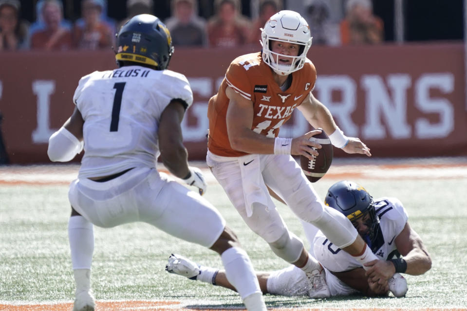 Texas' Sam Ehlinger (11) scrambles against West Virginia's Dylan Tonkery (10) and Tony Fields II (1) during the first half of an NCAA college football game in Austin, Texas, Saturday, Nov. 7, 2020. (AP Photo/Chuck Burton)