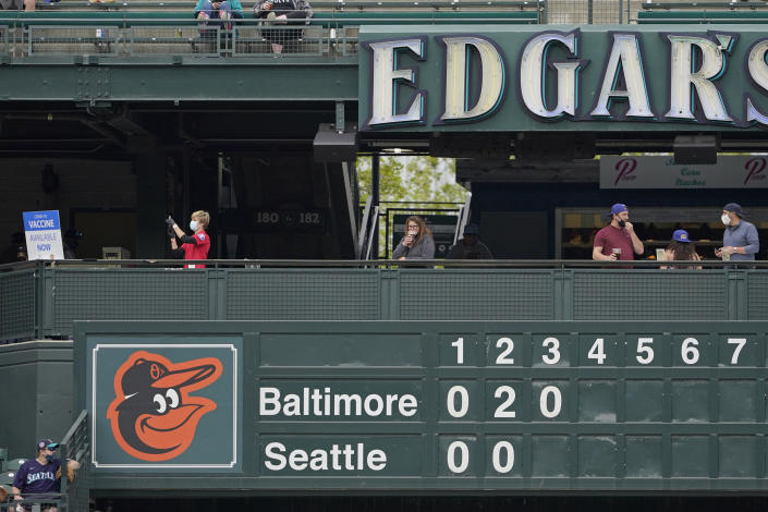 A Seattle Fire Dept. EMT, left, fills a syringe at a clinic administering free COVID-19 vaccines located above the manual scoreboard at T-Mobile Park during a baseball game between the Seattle Mariners and the Baltimore Orioles, Wednesday, May 5, 2021, in Seattle. The Mariners will be offering vaccines to eligible fans during upcoming home games. (AP Photo/Ted S. Warren)