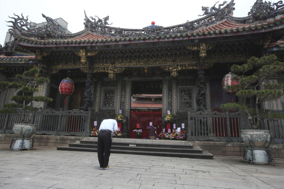 A visitor prays outside of Longshan Temple after the COVID-19 alert raise to level 3 in Taipei, Taiwan, Tuesday, May 18, 2021. (AP Photo/Chiang Ying-ying)